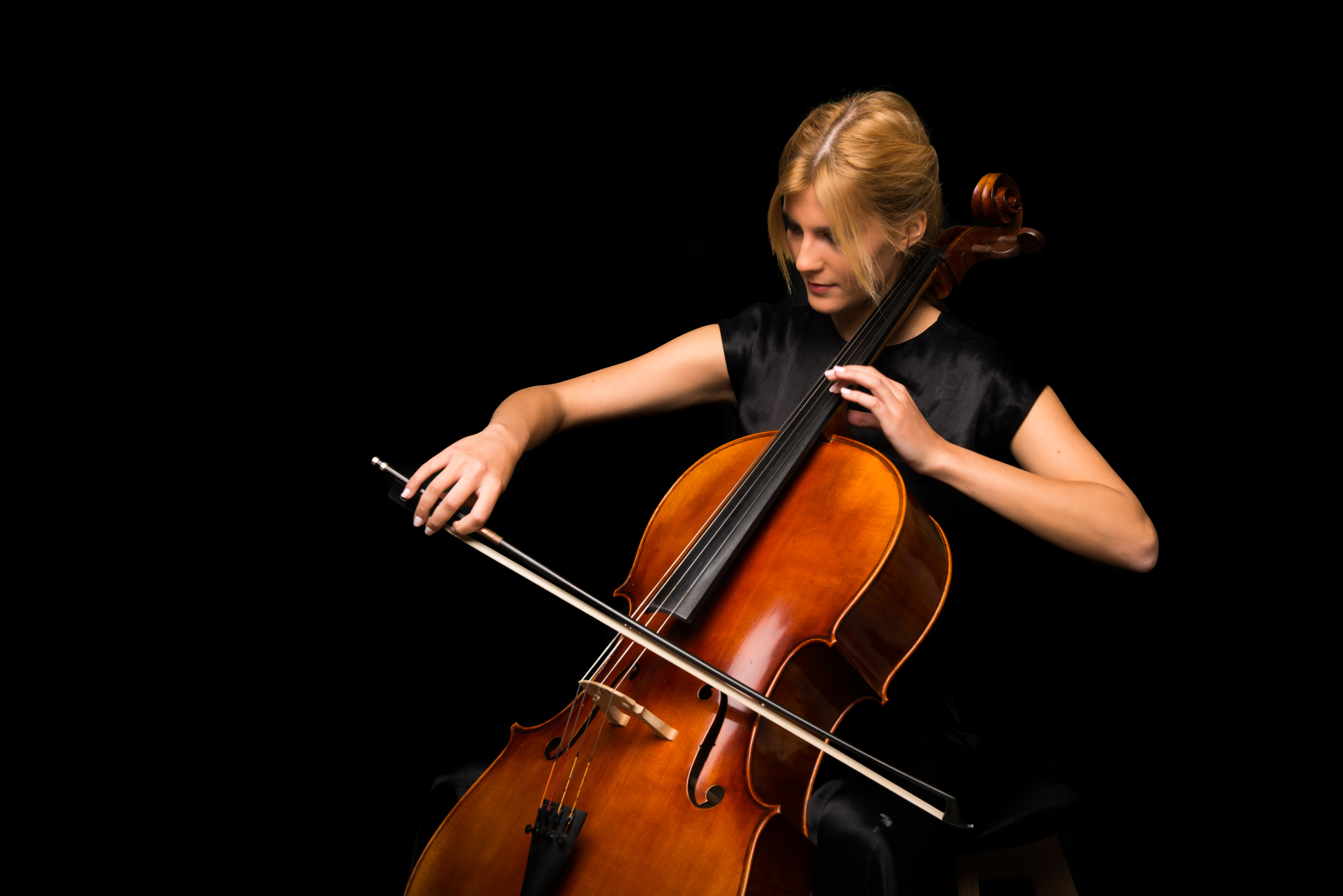 Young girl playing the cello on isolated black background