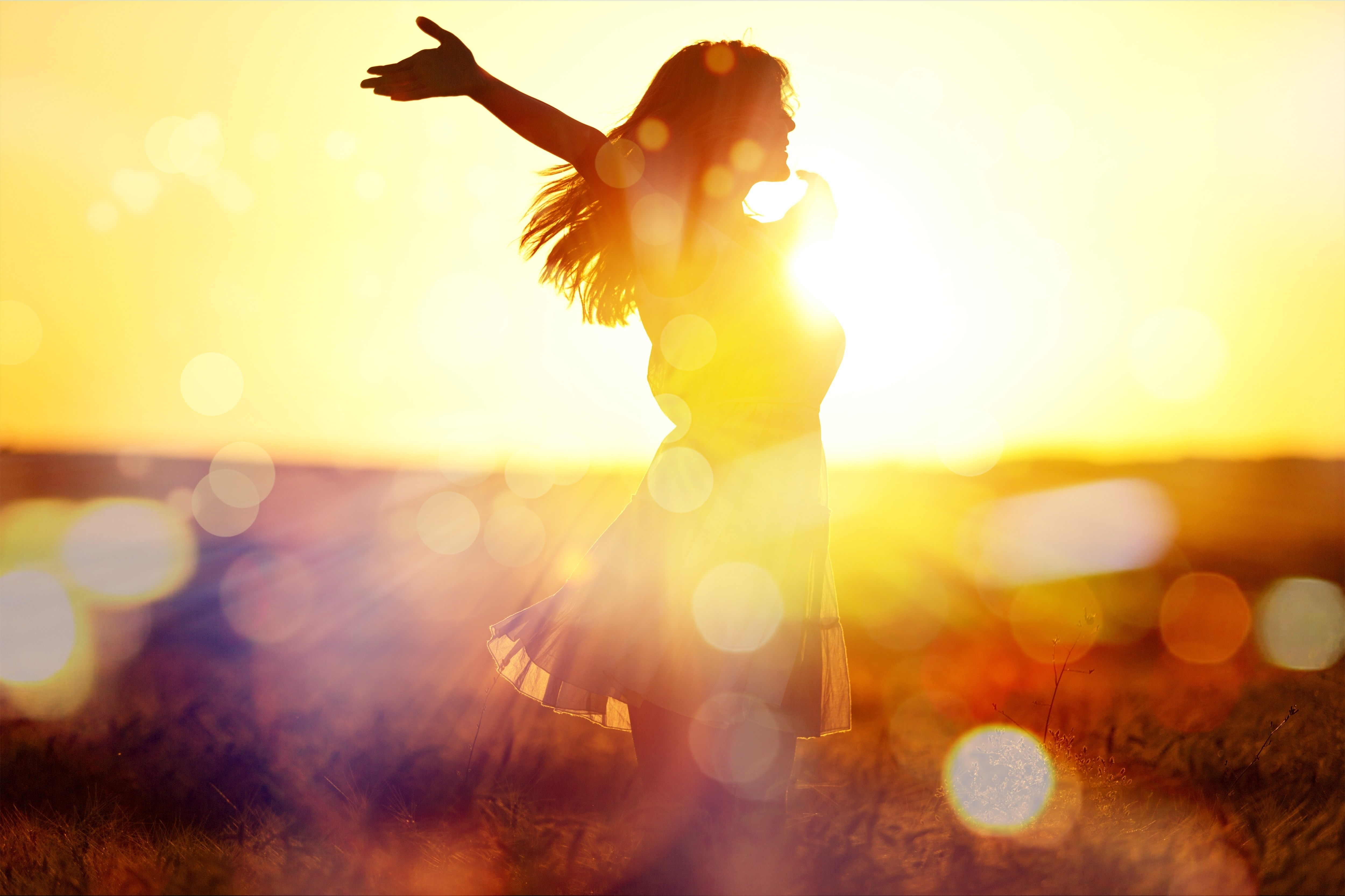 Young woman on field under sunset light